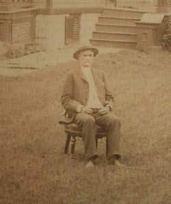 Jacob Miers sitting in a chair on the front lawn of his house.